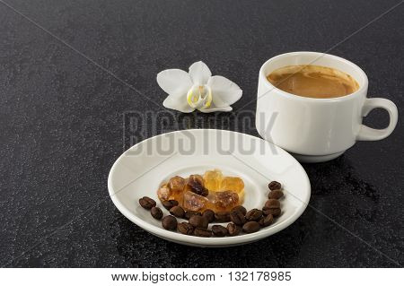 Romantic coffee cup and white orchid on the black background. Coffee break. Strong coffee. Coffee cup. Coffee mug. Morning coffee. Cup of coffee.