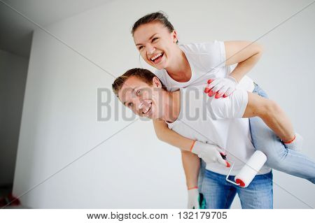 The young couple has fun doing repair in the apartment. The girl has got on a back to the guy. On faces cheerful smiles. Young people hold rollers for paint. Their hands in working gloves.
