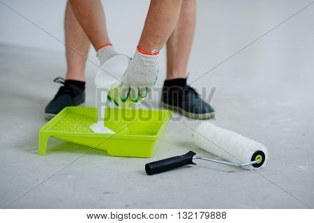 On the gray concrete floor is a yellow tray. Near him the roller for painting. Hands in working gloves pour into a tray white paint from jar. Strong male legs in black footwear are also visible.