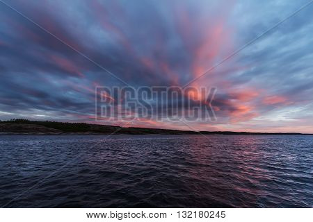 Amazing sunset over sea with pink sky and clouds in Russia