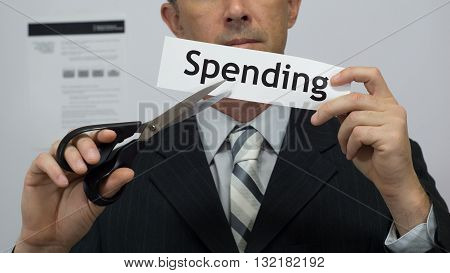 Male office worker or businessman in a suit and tie cuts a piece of paper with the word spending on it as a spending or expense reduction business concept.