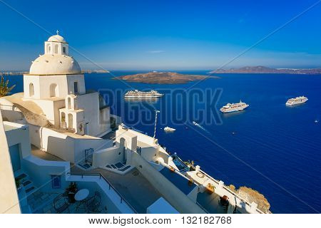 Fira, modern capital of the Greek Aegean island, Santorini, with orthodox church, cruise ships, caldera and volcano, Greece