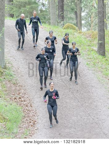 STOCKHOLM SWEDEN - MAY 14 2016: Group of woman in black training clothes running down a in the obstacle race Tough Viking Event in Sweden April 14 2016