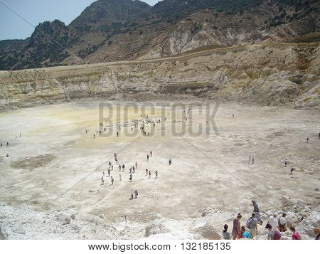 Stefanos crater. The volcano on the island of Nisyros. Greece. Tourists walking inside the crater.