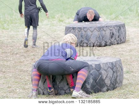 STOCKHOLM SWEDEN - MAY 14 2016: Rear view of woman struggling to tip a large tractor tire obstacle in the obstacle race Tough Viking Event in Sweden April 14 2016