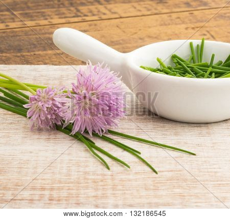 Square shot of home grown chopped chives in a white dish with purple flowers window lit for soft focus wood grain background.