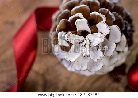 pinecone and red ribbon on wood for christmas