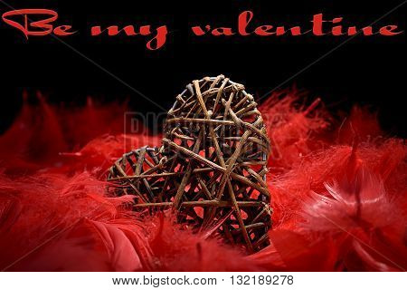 wooden heart in the midst of red feathers on a black background and be my valentine written