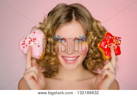 young woman with two donuts on pink background