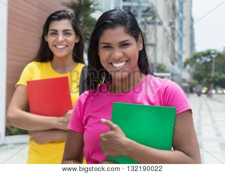 Two laughing latin female students outdoor in the city