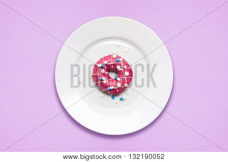 Creative concept photo of a donut covered with pills on a plate on pink background.