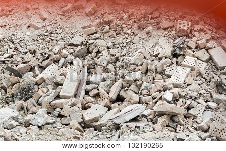 Bricks stacking with red color on top, as a sign of blood (victims at work)