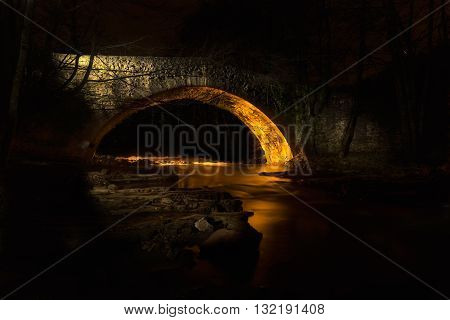 Old bridge iluminated with a torch at night