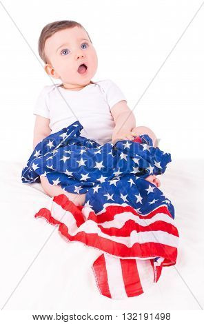 Baby girl with american flag on white sofa.