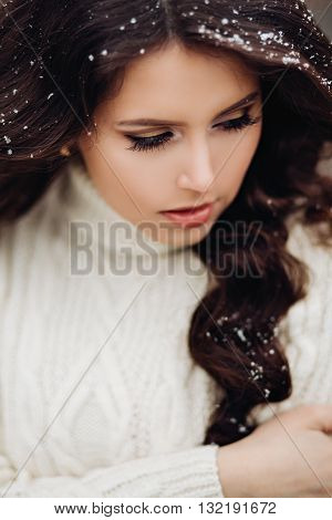 Portrait of beautiful young woman brunette beautiful long hair,white dress turtleneck,a fashionable Golden makeup.