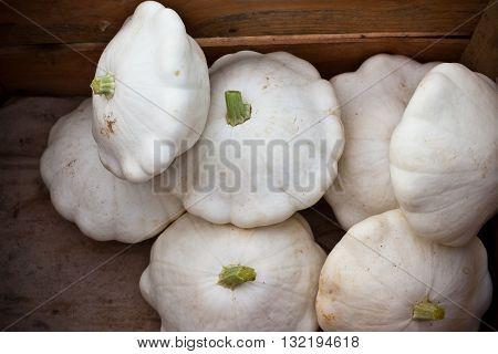 White custard marrows in a wooden box on a farm market