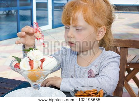 A little girl eating ice cream in the outdoor café