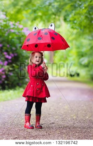 Little girl playing in rainy summer park. Child with red ladybug umbrella waterproof coat and boots jumping in puddle and mud in the rain. Kid walking in autumn shower. Outdoor fun by any weather.