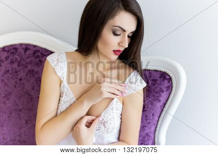 morning beautiful gentle girl in boudoir dressing gown bride bride fees with a large bouquet of roses waiting at the window