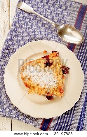 home made cherry crumble with powdered sugar on a white plate