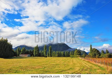Countryside in Chilean Patagonia. Green fields and mountain range