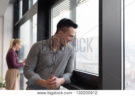 happy young business at modern office looking through window