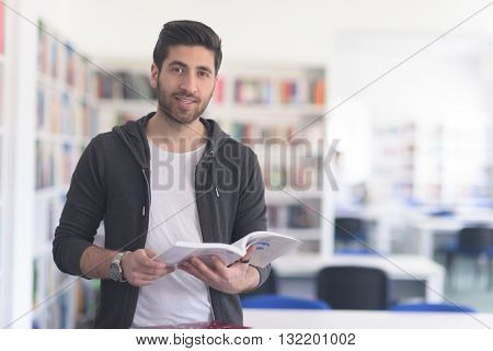 Portrait of happy student while reading book in school library. Study lessons for  exam. Hard worker and persistance concept.