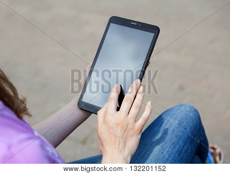 Woman's hands on a screen of a tablet gray background