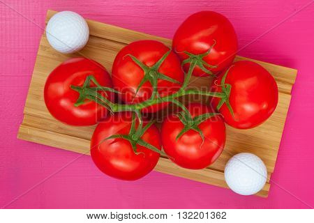 Golf breakfast - Red tomatoes and golf ball on the wooden desk