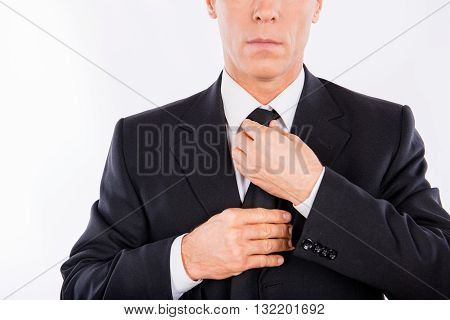 Close up photo of man in suit fastening his tie