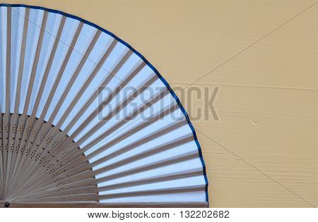 Typical Japanese hand fan made on the wooden yellow table