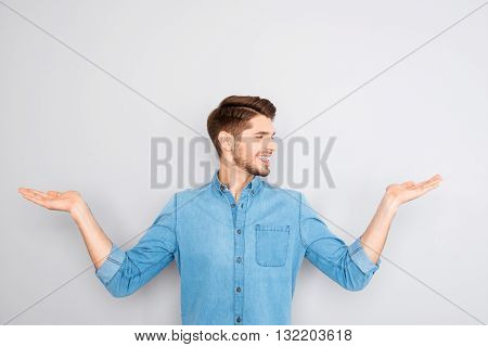 Cheerful Young Man Presenting Products In Both Hands