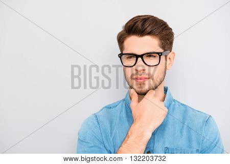 Young Calm Guy In Glasses Dreaming And Touching Chin