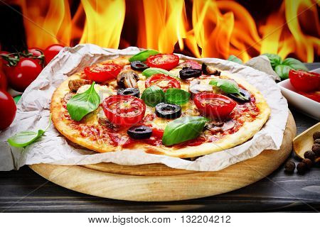 Tasty hot pizza with vegetables and basil on fire flame background