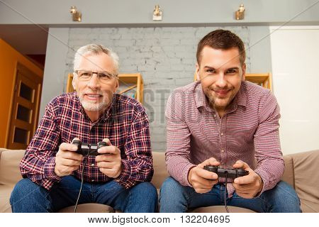 Happy Man And His Father Playing Video Games While Sitting On Sofa