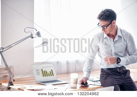 Real professional. Pleasant brutal handsome man leaning on the table and holding cell phone while being involved in work