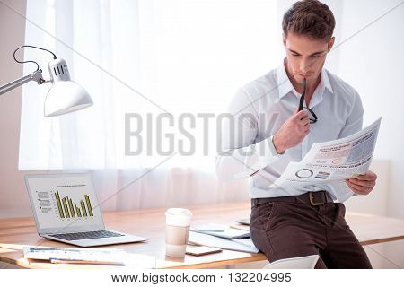 Get the information. Pleasant concentrated brutal man leaning on the table and reading newspaper while standing in the office