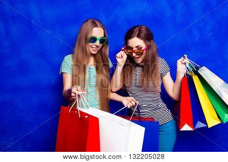 Young Girl Showing Her Purchases To Her Sister