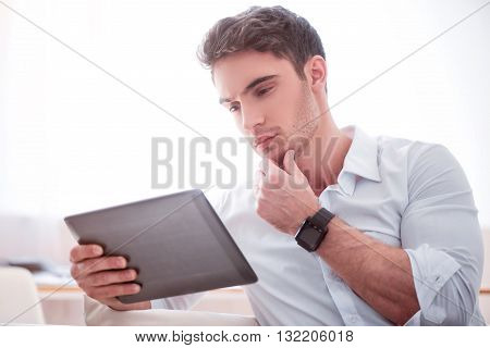 Let me think. Pleasant brutal serious handsome man sitting on the couch and thinking while using tablet