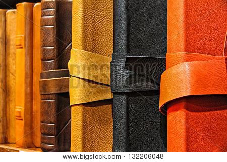 Book in leather cases of different colors are on the shelf