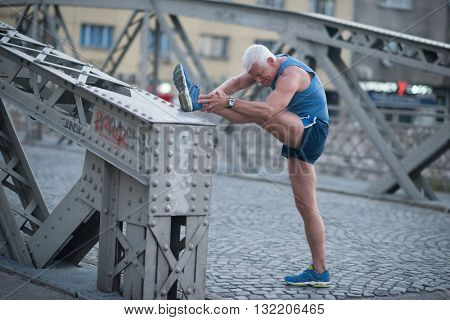handsome senior man stretching and warming up before jogging exercise at early mornig