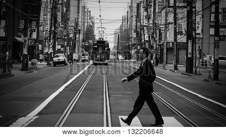 Man Cross Street While Tram Is Riding
