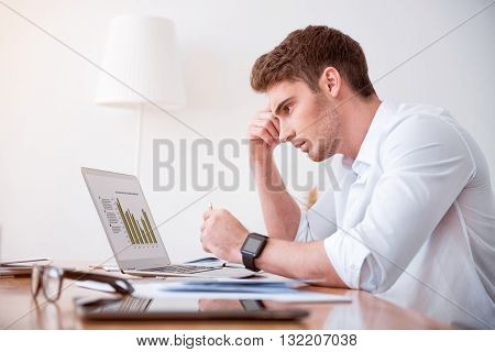 Concentrate on task.  Pleasant handsome serious, man sitting at the table and working on the laptop while being involved in work