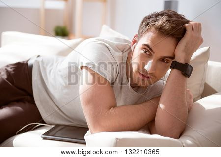 Involved in thoughts. Pleasant handsome brutal man listening to music and thinking while resting on the couch