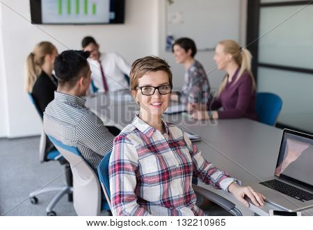 portrait of young business woman at modern startup office interior, team in meeting group in background