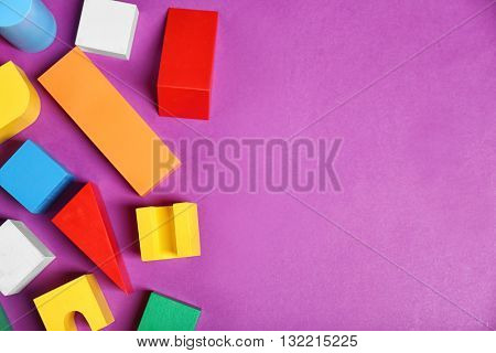 Colorful wooden kids toys on purple background