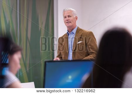handsome mature teacher and students in computer lab classroom