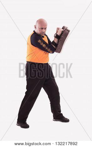 Martial arts trainer holding kick-shield. Studio shoot