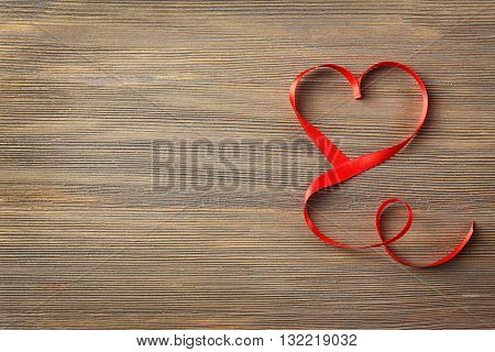 Red heart shaped ribbon on wooden background