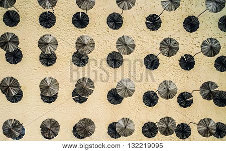 wooden sunshade umbrellas on a beach, top view, aerial photo